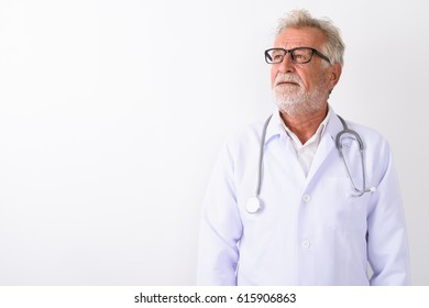 Studio shot of handsome senior bearded man doctor thinking while looking up against white background