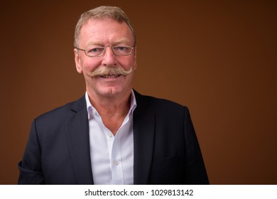 Studio shot of handsome senior businessman with mustache wearing eyeglasses against brown background
