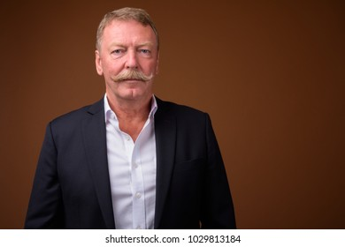 Studio shot of handsome senior businessman with mustache against brown background