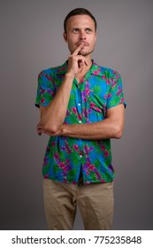 Studio shot of handsome tourist man ready for vacation against gray background