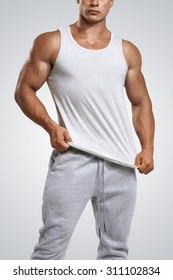 Studio shot of a handsome young fitness man wearing white blank tank top isolated on white background