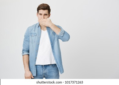 Studio shot of handsome young man in denim clothes closing his mouth with hand, seriously looking at camera, asking to keep his secret, not to tell anyone. Confidential information concept.