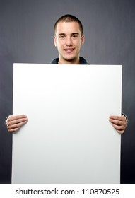 Studio shot of handsome young man with blank white board