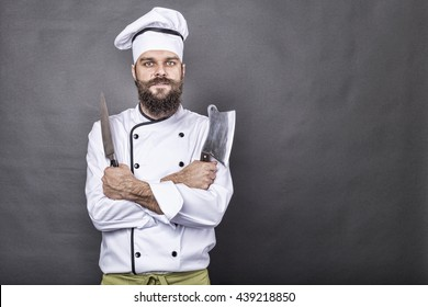 Studio shot of a happy bearded young chef holding sharp knives over gray background