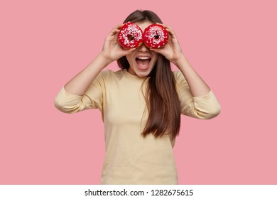 Studio shot of happy dark haired woman covers eyes with two red donuts, being in high spirit, wears yellow clothes, eats delicious junk food, has fun with friends. Female youngster holds doughnuts