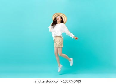 Studio shot of happy energetic asian woman wearing summer fashion attire jumping in mid-air motion isolated in light blue background