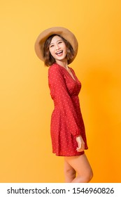 Studio shot of happy energetic asian woman wearing red dress and straw hat over orange background