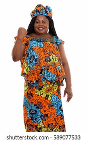 Studio shot of happy fat black African woman smiling and standing while wearing traditional clothes and looking motivated