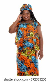 Studio shot of happy fat black African woman smiling  while standing and talking on mobile phone while wearing traditional clothes