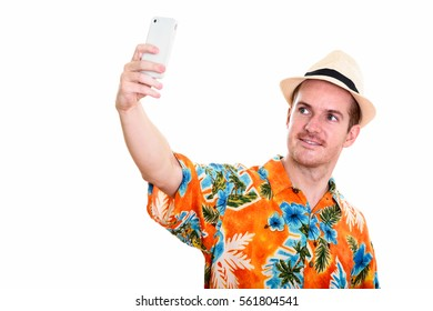 Studio shot of happy man smiling while taking selfie picture with mobile phone