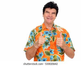 Studio shot of happy mature Caucasian man wearing Hawaiian shirt and giving thumbs up