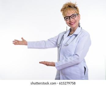 Studio shot of happy senior Asian woman doctor smiling while showing something and wearing eyeglasses against white background