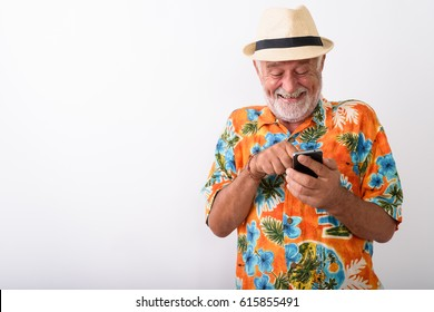 Studio shot of happy senior bearded tourist man smiling and giggling while using mobile phone against white background