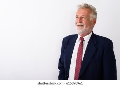 Studio shot of happy senior bearded businessman smiling while thinking against white background