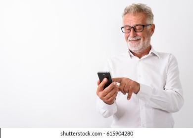 Studio shot of happy senior bearded businessman smiling while using mobile phone with eyeglasses against white background