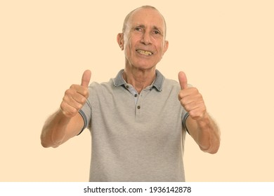Studio shot of happy senior man smiling and giving thumbs up
