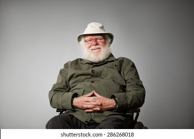 Studio shot of happy senior man sitting on wheelchair looking at camera smiling against grey background