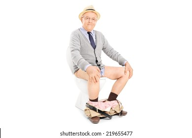 Studio shot of a happy senior seated on a toilet isolated on white background