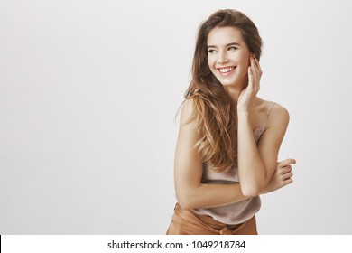 Studio shot of happy successful attractive european woman bending towards camera and gently touching face, looking left and smiling positively, feeling great and enjoying life over gray background