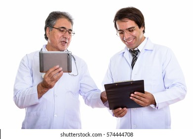 Studio shot of happy young and senior Persian man doctor smiling while holding digital tablet and reading on clipboard