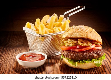 Studio shot of high burger with french fries in small fry basket and bowl of ketchup on wooden surface