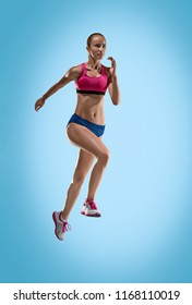 The studio shot of high jump athlete or fit woman in action i on blue background