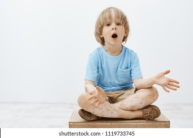 Studio shot of impressed curious blond child with vitiligo sitting with crossed feet and dropping jaw, spreading palms, being interested and questioned while hearing amazing stories from dad