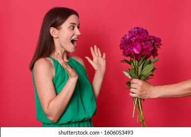 Studio shot of impressed sweet good looking brunette raising her hands, opening eyes and mouth widely, being surprised by present of bright peonies, unknown hand holding flowers. Present concept.
