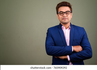Studio shot of Indian businessman wearing suit against colored background