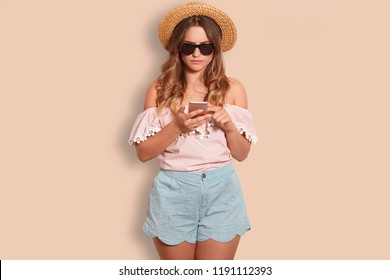 Studio shot of indignant displeased woman reads negative information on mobile phone, dressed in stylish clothes, poses against beige background alone. People and modern technologies concept
