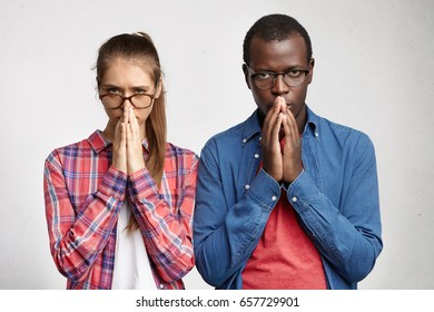 Studio shot of international couple of white woman and black man standing shoulder to shoulder and pressing their hands together, praying, asking God to put an end to animosity, violence and racism