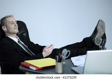 studio shot of isolated picture of a strange caucasian businessman with piercing and tattoos  listening multimedia player