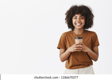 Studio shot of joyful carefree and friendly African American happy woman with afro hairstyle holding cup of coffee in both hands and smiling broadly while having interesting conversation