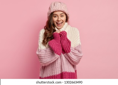 Studio shot of joyful pretty woman wears loose knitted pullover and hat, being in good mood after walk on frosty winter day, smiles broadly, isolated over pink concept. People, season concept