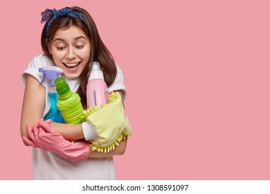 Studio shot of joyful young housemaid dressed in white t shirt, holds cleaning agents, smiles positively, isolated over pink studio background with copy space for your promotional or advert.