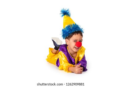 Studio shot of a little boy wearing carnival costume of a clown with a red round nose, isolate. Boy lying on the floor on his stomach