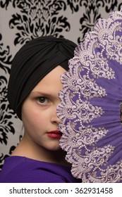 Studio shot of a little girl in a purple dress with a flapper hat and an oriental hand fan