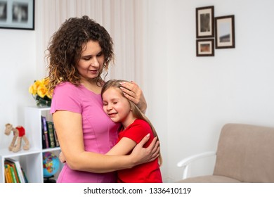 Studio shot of little girl smiling while hugging her mother tightly