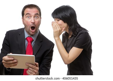 Studio shot of male and female co-workers using a tablet computer.  Female model is whispering into her male colleagues ear, leaving him with a startled expression.