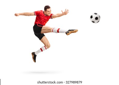 Studio shot of a male football professional kicking a ball in mid-air isolated on white background