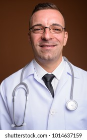Studio shot of man doctor wearing eyeglasses against brown background