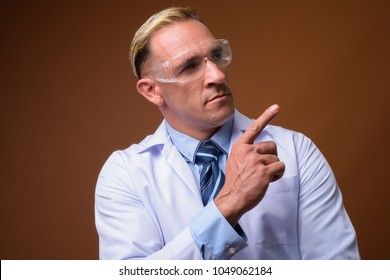 Studio shot of man doctor wearing protective glasses against brown background