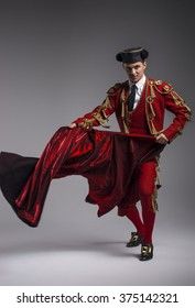 Studio shot of man dressed as Spanish torero, matador, bullfighter. Performing a traditional classic bullfight, standing and holding the capote.