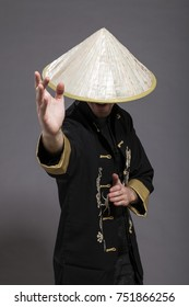 Studio shot of a man in his late twenties, wearing traditional chinese clothing and Kung-Fu posture; identity hidden.