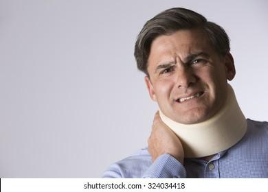 Studio Shot Of Man In Pain Wearing Neck Brace