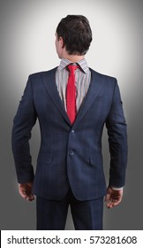Studio shot of a man wearing his suit on backwards, gray background