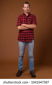 Studio shot of man wearing red checkered shirt against brown background