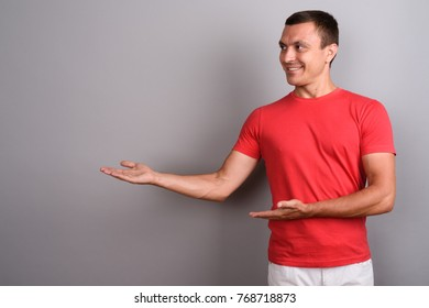 Studio shot of man wearing red shirt against gray background