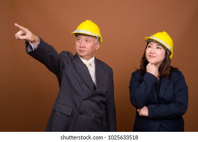 Studio shot of mature Asian businessman and mature Asian businesswoman wearing hardhat together against brown background