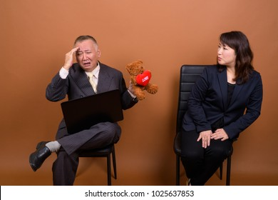 Studio shot of mature Asian businessman and mature Asian businesswoman together against brown background